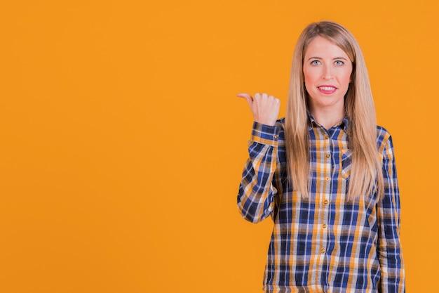 オレンジ色の背景に対して親指ジェスチャーを示す幸せな若い女の肖像