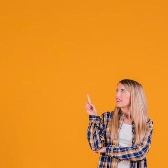 オレンジ色の背景に対して見上げて上向きに彼女の指を指している若いブロンドの女性