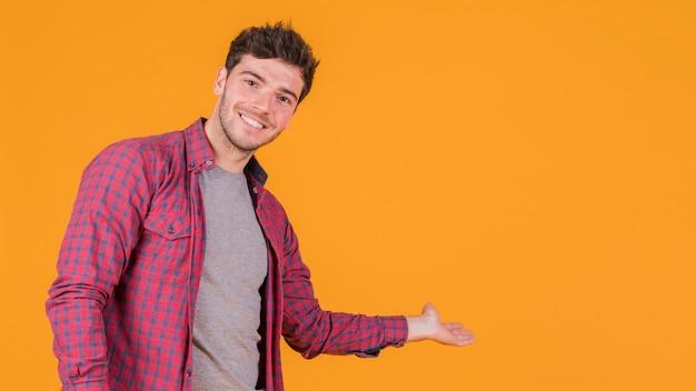 オレンジ色の背景上に何かを提示する若い男の笑みを浮かべてください。