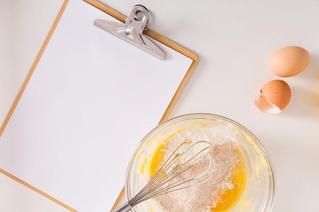 白い背景の上のホイップエッグと小麦粉ボウルクリップボードに白い空白の紙