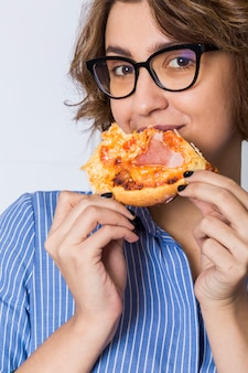 Молодая женщина ест пиццу, изолированных на белом фоне, глядя в камеру