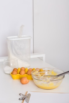 ホイップエッグ。卵のカートン。小麦粉;塩と紙の上のテーブルの上のクリップボード