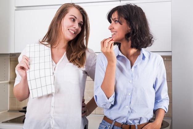 女友達が台所に立っているお互いを見て