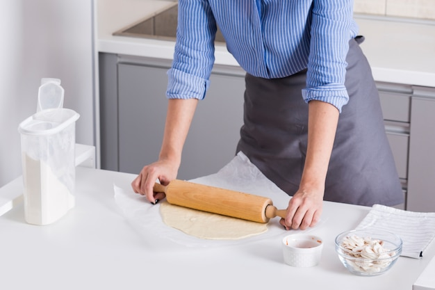 若い女性のクローズアップは、白いテーブルに麺棒で生地を平らに