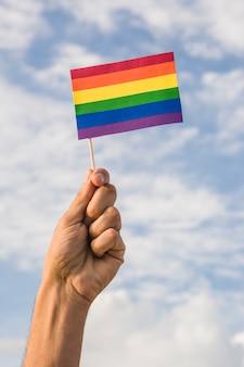 Мужчина держит флаг в цветах лгбт и голубое небо