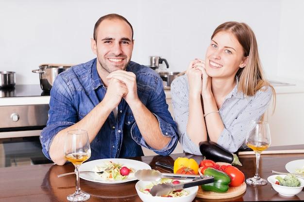 カメラを一緒に見て朝食を食べて笑顔の若いカップル
