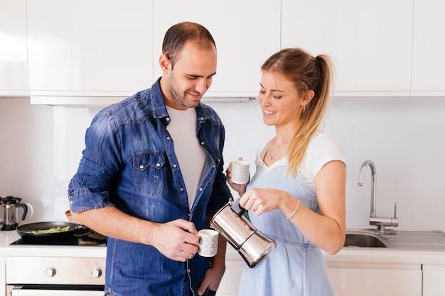 台所で彼氏によって保持カップでコーヒーを注ぐことを笑顔の若い女性