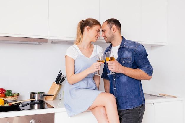 ロマンチックな若いカップルは台所で使い捨てからすを乾杯笑顔
