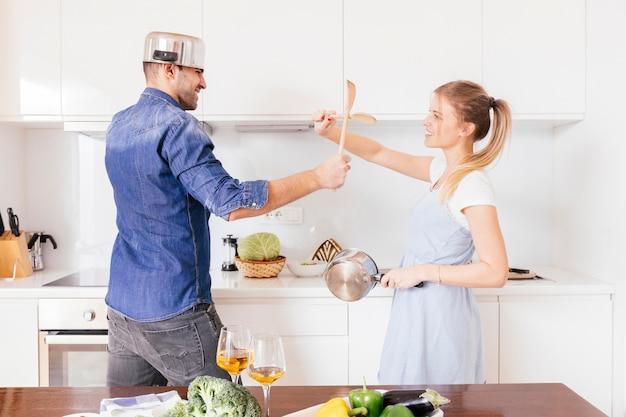 台所で楽しんで道具との戦い笑顔の若いカップルの肖像画