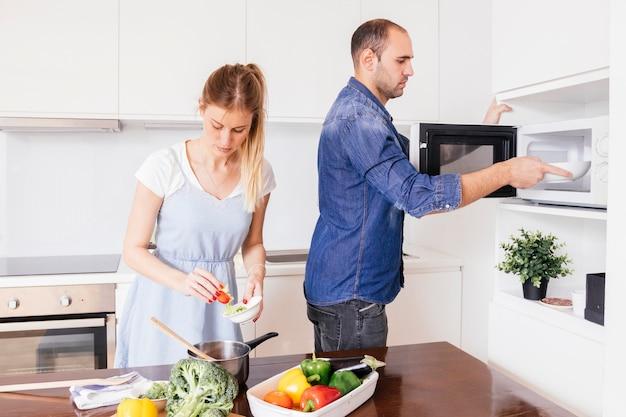 Молодой человек помогает жене готовить еду на кухне