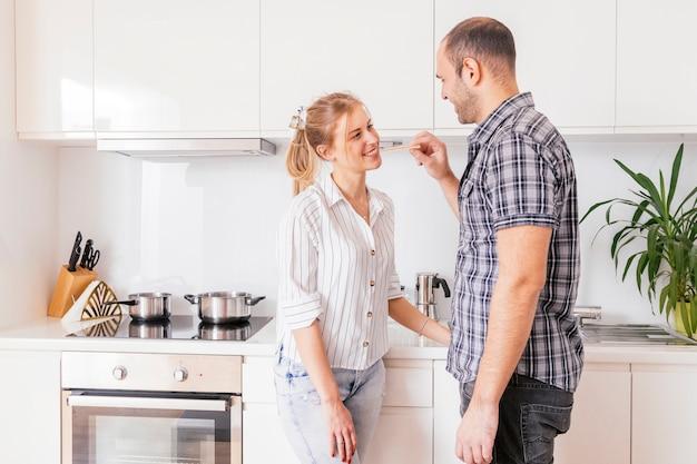グラハムクラッカーを台所で彼のガールフレンドに供給若い男のクローズアップ