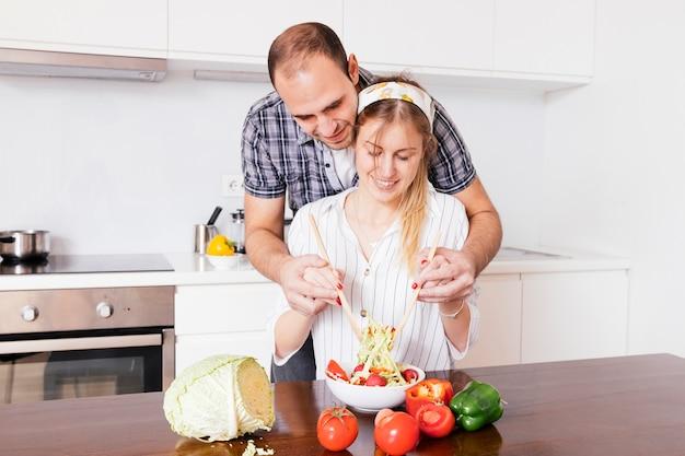 彼女の妻が台所でサラダを準備するのを助ける人
