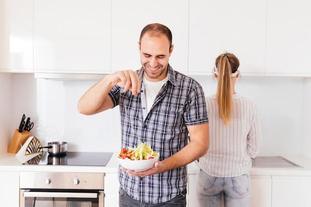 男は台所で新鮮なサラダボウルに塩のピンチを追加