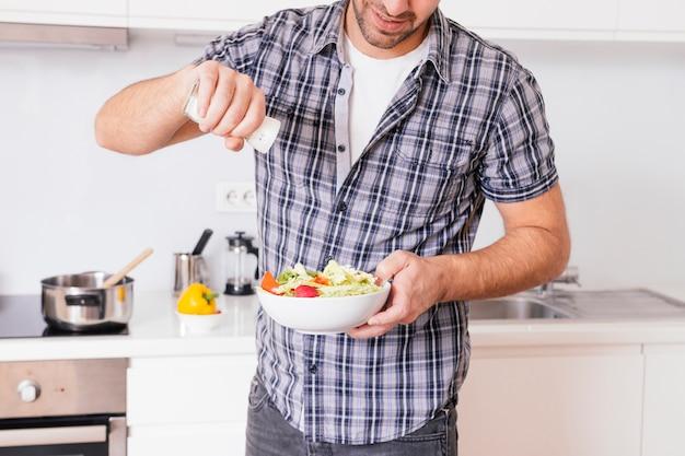 Конец-вверх молодого человека добавляя соль к овощному салату пока варящ в кухне