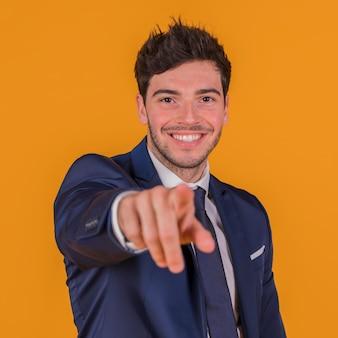 Красивый молодой человек, указывая пальцем на камеру на оранжевом фоне