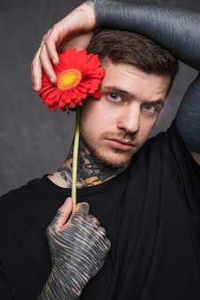 カメラを探している彼の耳の近くの花を持って彼の鼻にピアスを持つ若い入れ墨男