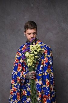 灰色の壁に対して紫と黄色のリモニウムの花を持って彼の手に入れ墨をしたヒップスター