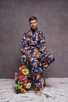 灰色の壁に対してカメラを見て手に花の花束を持って深刻な若い男