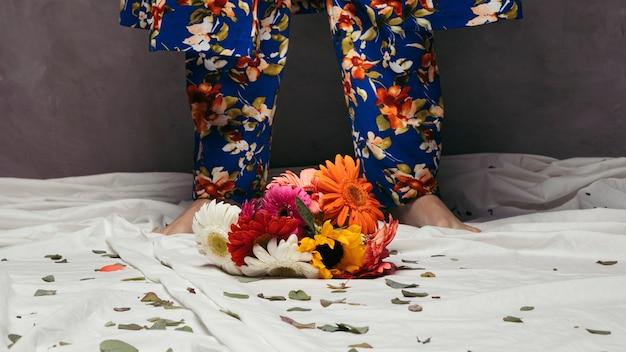 男の足の前にカラフルなガーベラの花