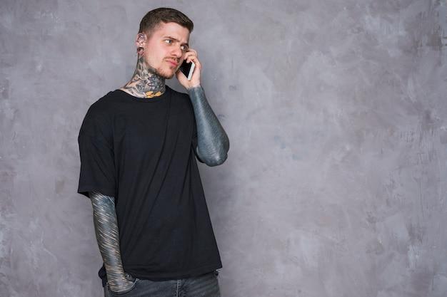 灰色の壁に対して携帯電話で話している彼の手に刺青を持つ怒っている若い男