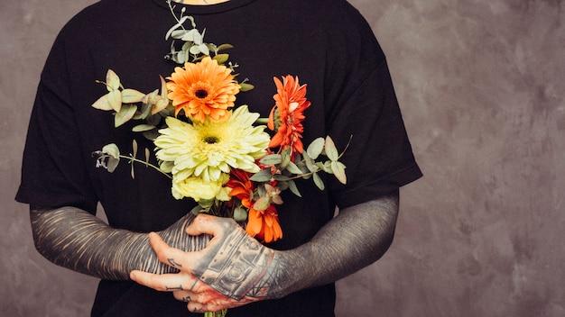 Средняя часть мужчины с татуировкой в руке держит букет гербер