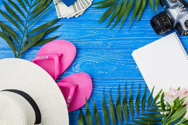 フリップフロップと植物の葉の間でメモ帳が付いている帽子の近くのカメラ