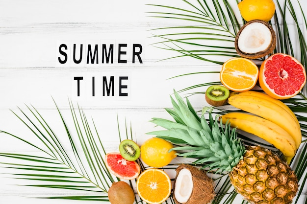 Название летнего времени среди листьев растений возле тропических фруктов
