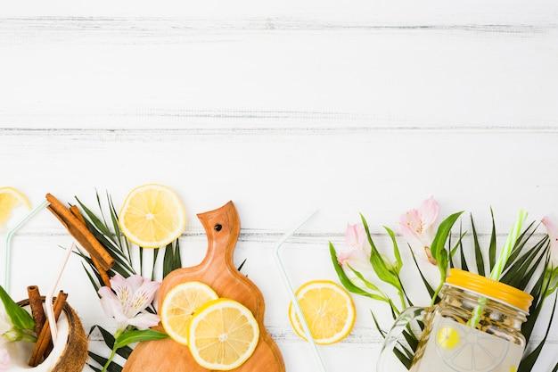 新鮮なレモンとまな板と植物の葉の近くのガラス
