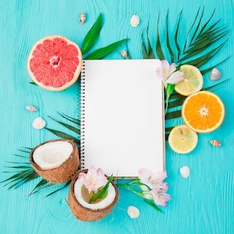 ボード上のノートブックと新鮮なエキゾチックなフルーツの近くの植物の葉