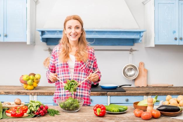 Портрет улыбающейся молодой женщины, готовящей овощной салат на кухне