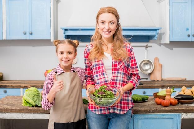 サラダのボウルを保持している彼女の母親と一緒に立っているサインを親指を示す笑顔の娘のクローズアップ