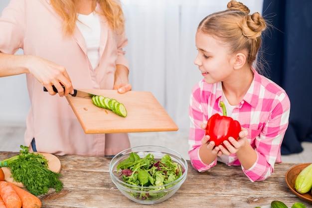 テーブルの上のサラダを準備する彼女の母親を見て微笑んでいる女の子