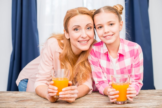 母と彼女の娘のジュースのガラスを保持している笑顔の肖像画