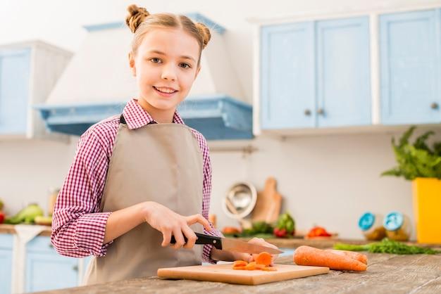 カメラ目線のテーブルにナイフでニンジンを切る微笑んでいる女の子の肖像画