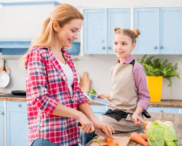 ナイフで彼女の母親切削ニンジンを見てテーブルの上に座って微笑んでいる女の子