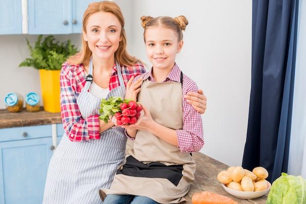 母と娘が台所でカメラを見ての肖像画