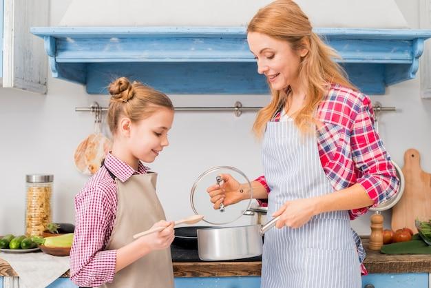 金髪の笑みを浮かべて女性が台所で彼女の娘に鍋を見せて