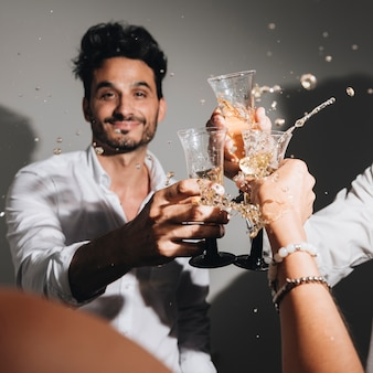 パーティーの男の子がシャンパンでポーズ