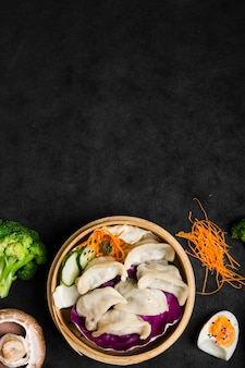 Китайские пельмени подаются на традиционном пароварке с салатом и вареными яйцами