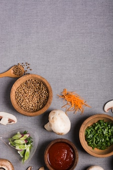 Деревянная чаша из зеленого лука; семена кориандра; соус; гриб и тертая морковь на серой льняной скатерти