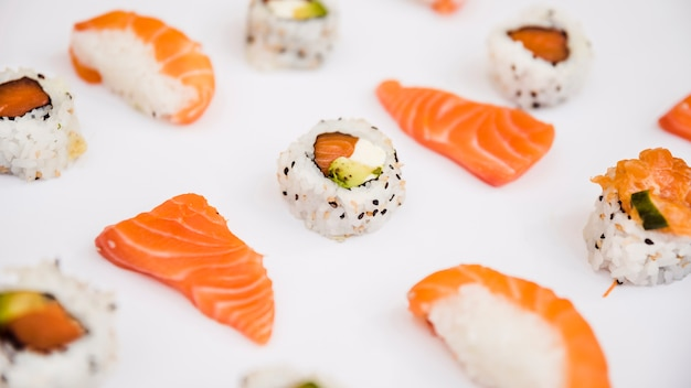 Ломтик лосося и суши на белом фоне