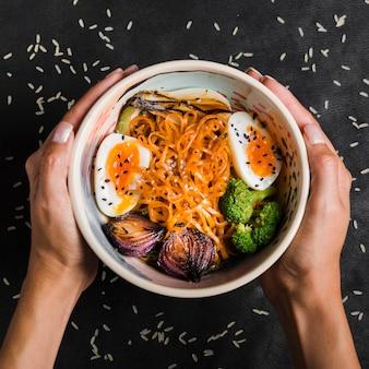 卵と麺のボウルを持っている女性の手のクローズアップ。玉ねぎ;黒の背景上にボウルにブロッコリー