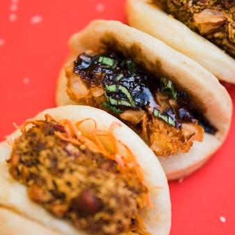 Азиатский гуа бао с курицей гриль и соусом терияки на красном фоне