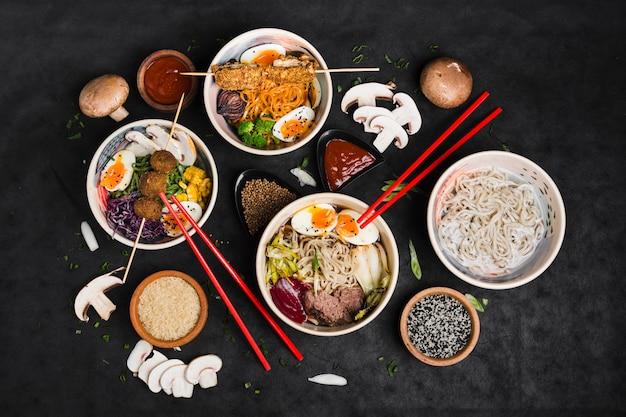 黒の背景に食材とチョッピングスティック麺のボウル