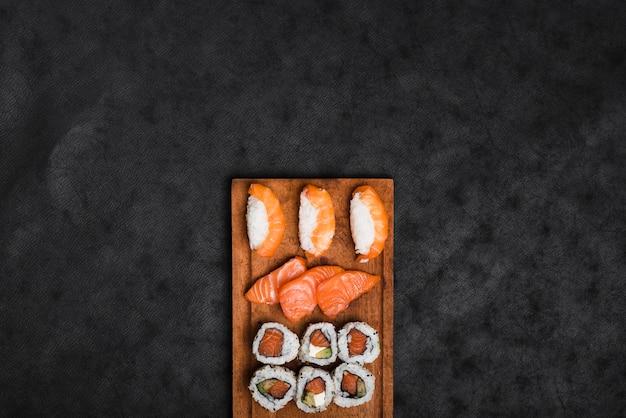 黒のテクスチャ背景に対して木製トレイに寿司の品揃え