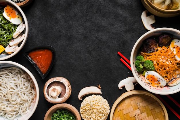 ソースと野菜の黒の背景に麺
