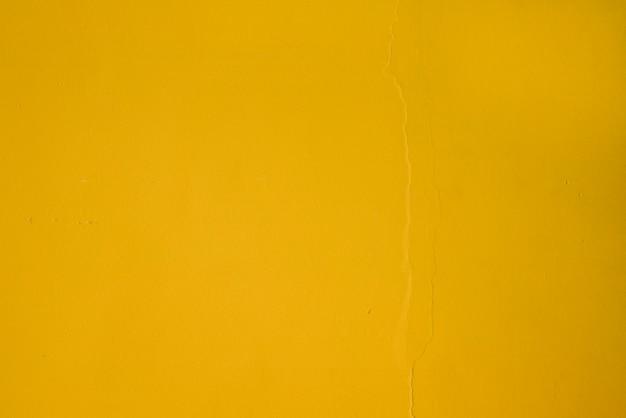 黄色の織り目加工の壁の背景のフルフレーム
