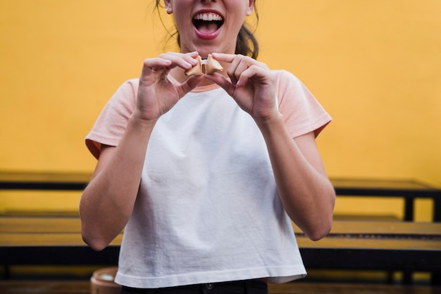メッセージを明らかにするためにフォーチュンクッキーをクラックする若い女性の肖像画