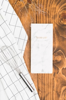 織り目加工の板の上に泡立て器と市松模様のナプキンを使ってメモ帳をする