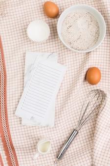 キッチンナプキンの上の空のチェックリストと健康的なベーキング成分
